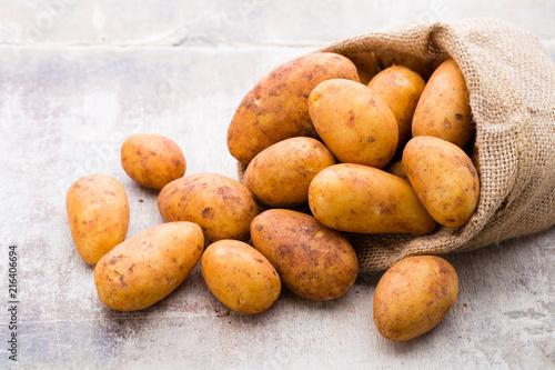 Poster A bio russet potato wooden vintage background.