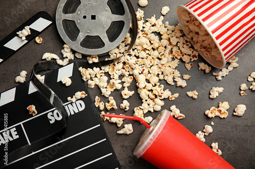 Leinwandbild Motiv Flat lay composition with popcorn, film reel and clapperboard on grey background