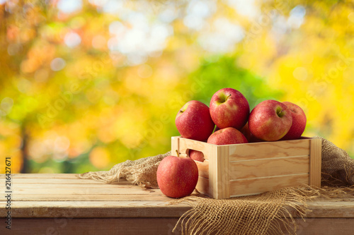 Red apples in wooden box on table - 216427671