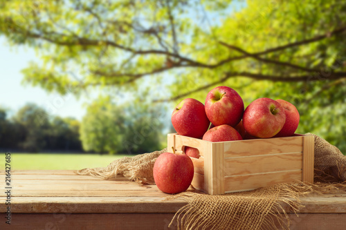 Red apples in wooden box on table - 216427685