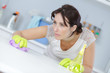 beautiful woman in protective gloves cleaning kitchen cabinet - 216432291