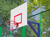 Basketball backboard against green trees