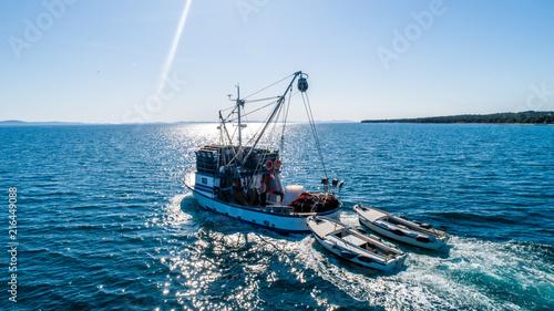 Fototapeta Fishing boat pulling two other smaller fishing boats
