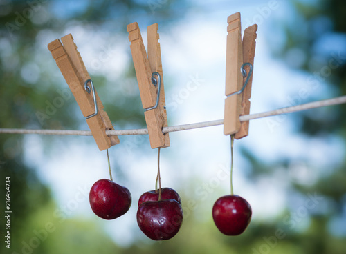 Foto Spatwand Kersen whimsical image of bing cherries on a clothes line. There is a soft focus green and blue background . The fruit is hanging with a clothes pin.