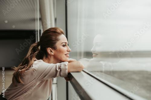Bocznego widoku szczęśliwa kobieta marzy podczas gdy patrzejący okno salowego. Odpoczywa podczas porodu