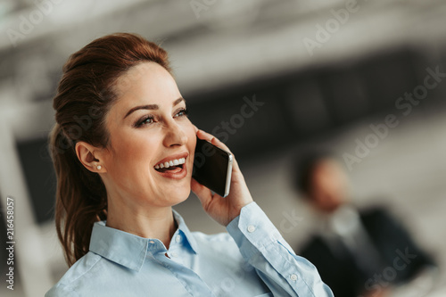 Leinwanddruck Bild Portrait of laughing woman talking on phone during job. Glad businesswoman during communication concept