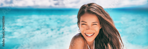 Leinwanddruck Bild Beautiful Asian woman smiling relaxing on summer beach sunbathing banner panorama.