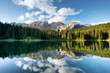 Mountains and forest reflection on the water surface. Natural landscape in the Dolomites Alps in the Italy