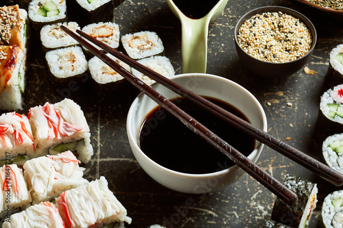 Foto Spatwand Sushi bar Close-up view of bowl of soy sauce with wooden chopsticks on the top
