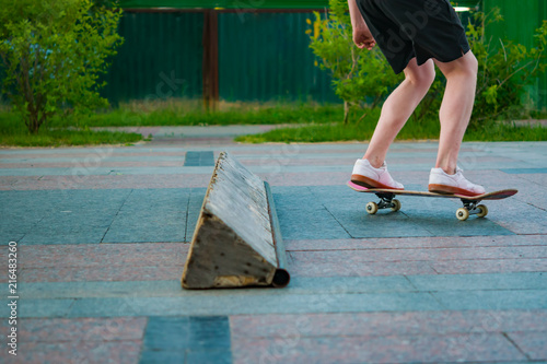 Foto Spatwand Skateboard Feet of skateboarder perform stunts in city Park, street youth sports, healthy life concept