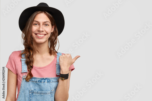 Leinwanddruck Bild Horizontal shot of positive female ranch owner indicates at her property, shows garden with rich harvest, has happy expression, wears elegant black hat, isolated on white studio wall with blank space
