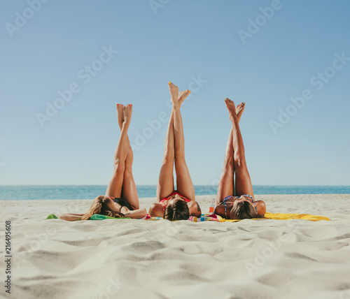 Leinwandbild Motiv Woman in bikini sunbathing on beach with legs raised to the sky