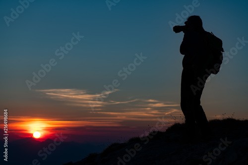 Foto Spatwand Groen blauw Photographing the sunset in the mountains. Photographer in silhouette