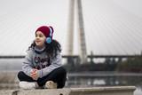 Niña escuchando música sentada al lado del río junto al puente de la ciudad - 216499884