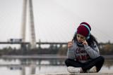 Niña escuchando música sentada al lado del río junto al puente de la ciudad