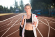 Beautiful girl in sporty top and legging dreamily looking in camera with backpack on shoulder and bottle of water in hand on racetrack of stadium