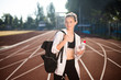 Pretty girl in sporty top and legging dreamily looking aside with backpack on shoulder and bottle of water in hand on racetrack of stadium