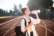 Beautiful girl in sporty wear with backpack on shoulder drinking water on racetrack of stadium