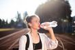 Portrait of beautiful girl in earphones drinking water on running track of stadium