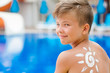 Sun painted by sun cream on boy shoulder. Summer vacation concept. Space for text - 216508439