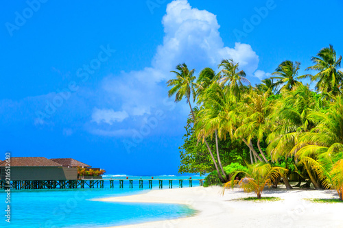 Fotobehang Bali Water villas in turquoise ocean and wooden walkway leading to the island with white beach and palm trees