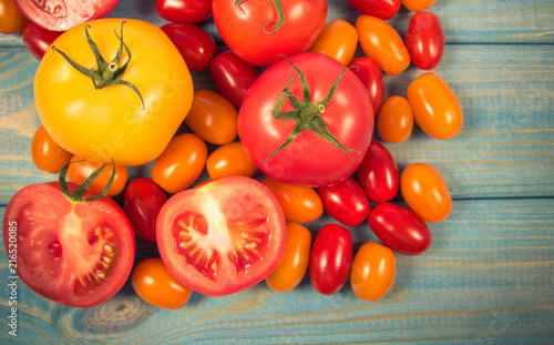 Foto Spatwand Kersen Different varieties of tomatoes on a blue wooden background.