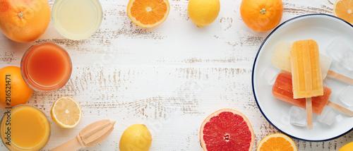 Canvas Sap Homemade orange and lemon popsicles and citrus fruits on stone black background.