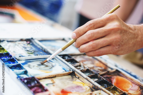 Foto Murales Artist hand with brush and watercolor palette with paints during drawing.