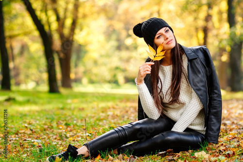 portrait of beautiful autumn girl in the Park, cute girl sitting in nature relaxing