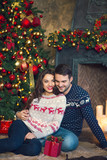 Man hugging happy girlfriend with Christmas present
