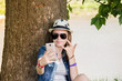 Quadro happy teenage girl with glasses and hat to make selfie in nature background