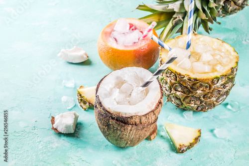Foto Murales Summer holiday drink concept, set various tropical cocktails or juices in pineapple, grapefruit and coconut with ice, light blue concrete background copy space