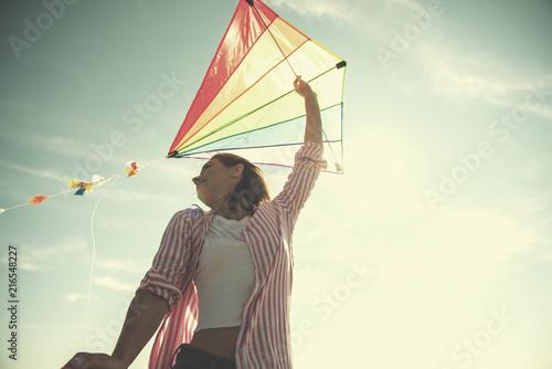 Leinwandbild Motiv Young Woman with kite at beach on autumn day