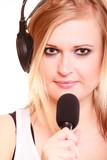 Woman singing to microphone wearing headphones - 216563281