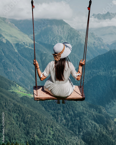 Leinwanddruck Bild Freedom and carefree of a young female on a swing