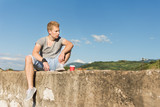 Handsome blond young man relaxing outdoors, with takeaway coffee, sitting on concrete wall listening to music. Natural lighting, no retouch, copy space - 216570428