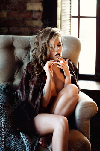Leinwanddruck Bild Beautiful sexy lady smoking in black coat