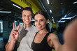 Leinwandbild Motiv Portrait of satisfied man and woman taking their own photo after workout. Smiling girl is holding gadget for shooting while guy is grinning and expressing v gesture. Enjoying active time with partner