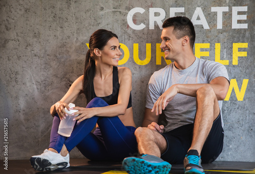 Leinwandbild Motiv Positive guy is coGrinning couple is relaxing and sitting on floor in sport center after workout. They are having pleasure while chatting and resting. Woman is holding flask with water for quenching