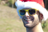young girl smiling with sunglasses and santa claus hat in summer
