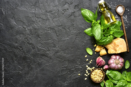 Ingredients for making traditional italian sauce pesto : basil leaves, parmesan cheese, olive oil, garlic, pine nuts and sea salt. Top view with copy space. - 216577839