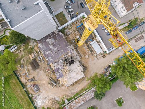 żółty dźwig wieżowy do budowy nowego wieżowca. antenowy widok z góry