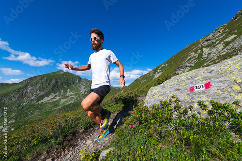 Male athlete practicing mountain running on a trail marked by the orobic alps