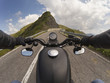 hairpin bends in the mountains with the handlebars of a motorcycle in the foreground