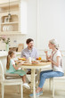 Cheerful talkative young family in casual clothing enjoying breakfast and communication while sitting at table sharing stories in cozy kitchen