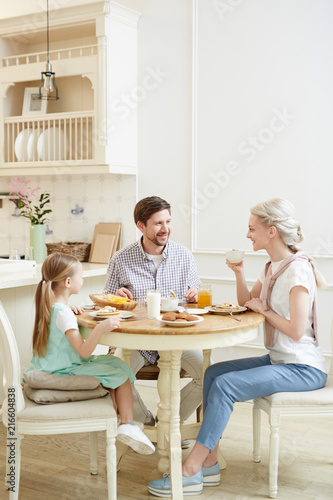 Cheerful talkative young family in casual clothing enjoying breakfast and communication while sitting at table sharing stories in cozy kitchen - 216604838
