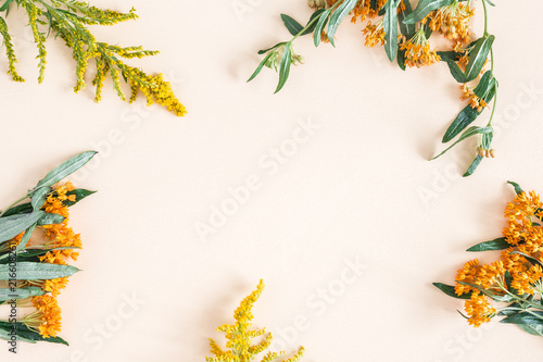Autumn composition. Frame made of fresh orange and yellow flowers on pastel beige background. Autumn, fall concept. Flat lay, top view, copy space - 216608261