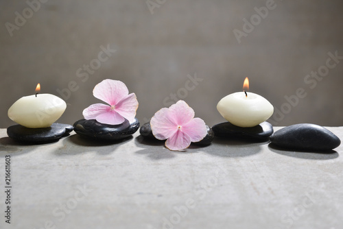 Plexiglas Spa Pink hydrangea petals with white candle on gray background