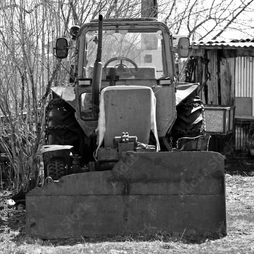 Foto Spatwand Trekker The old thrown tractor with chains on wheels. Black and white style.