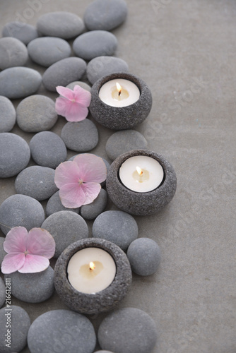 Plexiglas Spa Pile of gray stones with three candle with Pink hydrangea petals and grey background